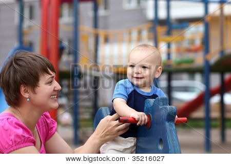 Smiling Child On Wooden Horse
