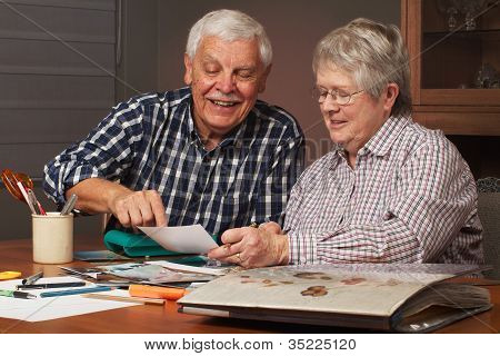Happy Senior Couple Making A Scrapbook