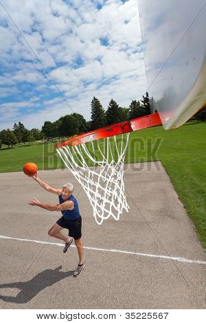 Happy active retired man in his 60s playing basketball outdoors