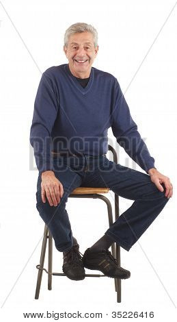 Happy Senior Man Sits With Hands On Knees.