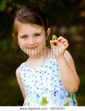 Outdoor portrait of cute young girl holding flower in park