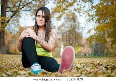 Knee injury - woman sitting in pain