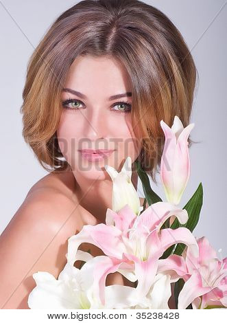 Beauty face of the young woman with pink lilly