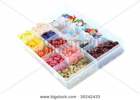 Multiple color buttons focus near in plastic box on white background.