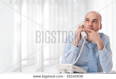Businessman Talking On Landline Phone At Office