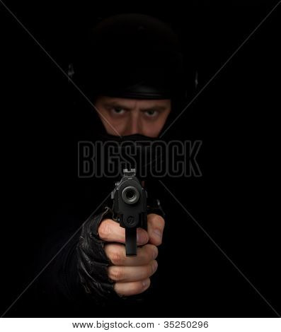 Assassino armado com capacete de motocicleta apontando para a câmera