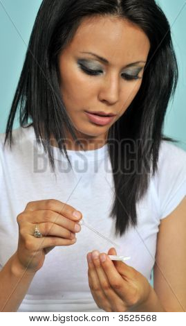 Woman Reading A Pregnancy Test Strip