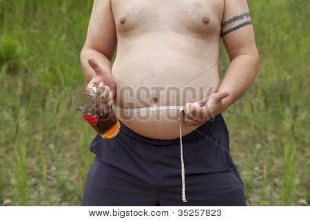 Fat man with a beer in hand and a tape measure around