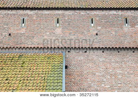 Old Town-wall Of Bricks And Two Roofs With Tiles