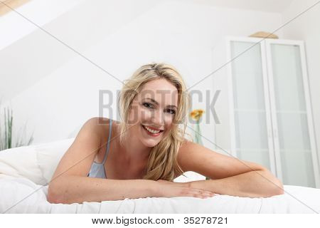 Friendly Smiling Woman On Her Bed