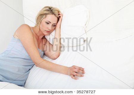 Sick Depressed Woman Propped Up On Pillows