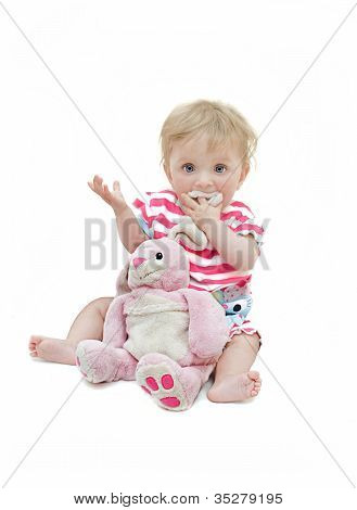 Baby girl holding a cuddly toy.