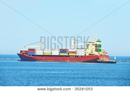 Tugboat assisting cargo ship