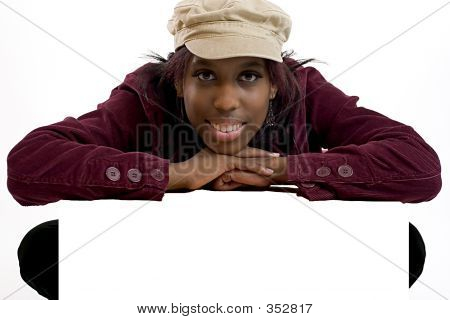 Young Black Woman Leaning Over A Blank Sign For Copy Space