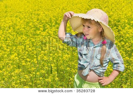 The little girl in the hat among the blossoming of the field.