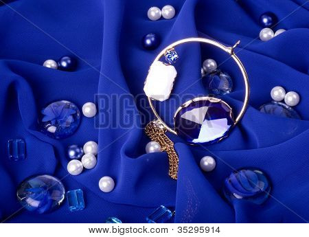 Gold jewelry and costume jewelry on a dark blue background