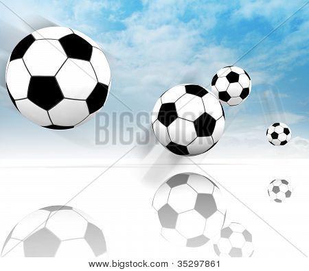 Four Football Balls On Clear Spacious Field With Blue Sky
