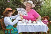 stock photo of polite girl  - A charming spring garden is a perfect setting for a loving grandmother and her 6 year old granddaughter to have a tea party - JPG