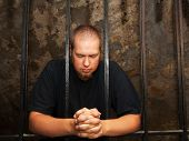 stock photo of repentance  - Young man praying staying behind the bars - JPG