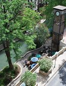 Tourist Couple Dine On Riverwalk Patio poster