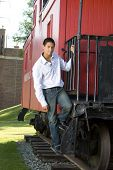 pic of caboose  - Attractive teenage boy standing on the steps of a red caboose - JPG