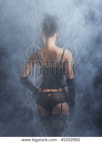 Back and buttocks of young woman in retro lingerie over the smoky background