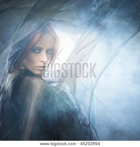 Young attractive woman in blowing silk over the smoky background