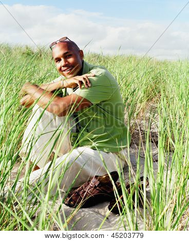 Young man sitting in sea grass on beach (slight grain)