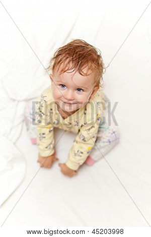 Joyful Little Girl Sitting On Bed And Looking Up At The Camera