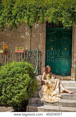 Life In Provence. Woman Sitting On The Porch And Stroking A Cat