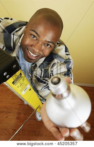Portrait of man changing a light bulb