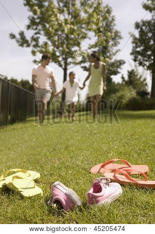 Family walking in park with shoes off