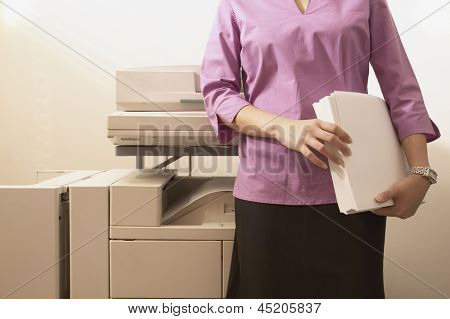 Midsection view of woman standing in front of photocopier