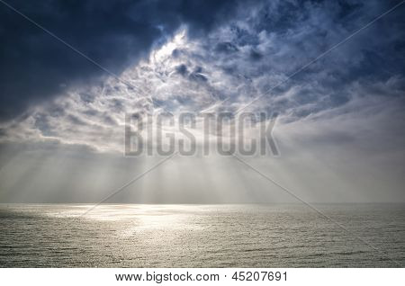 Beautiful inspirational sun beams over ocean on cloudy day