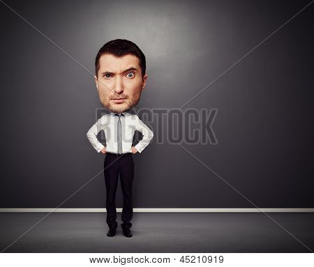 full-length funny picture of businessman with big head over dark background