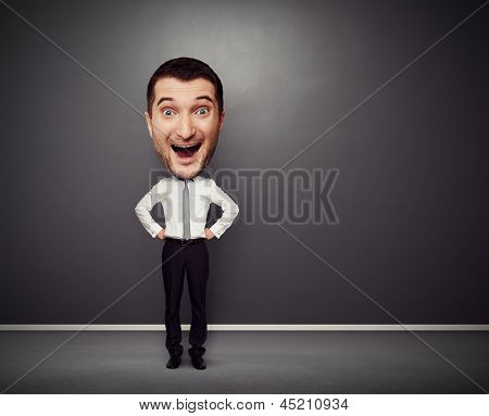 full-length picture of excited businessman with big head over dark background