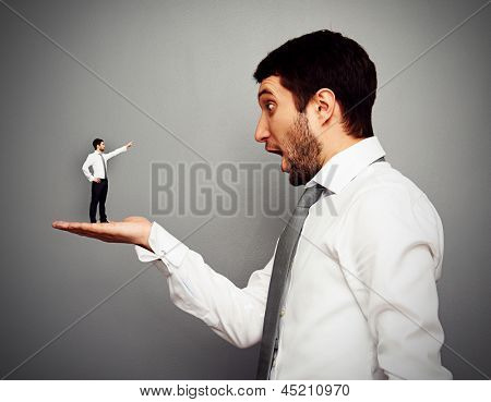small man pointing at the amazed big man. concept photo over dark background