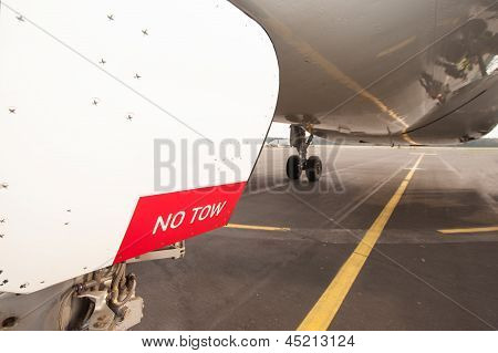 Sign No Tow On Undercarriage Of Airplane - Jetplane Waiting On Runway