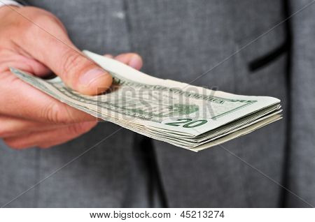 a man wearing a suit with a wad of dollars in his hand