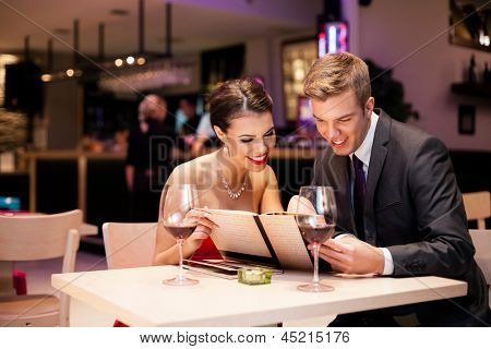 Couple reading  at menu together in a restaurant