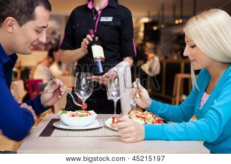 young couple nice dinner in a restaurant - waiter offers wine