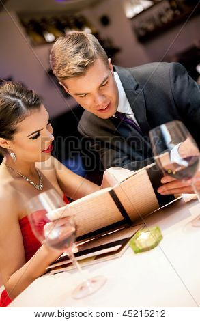 Couple choosing meal from the menu card in restaurant