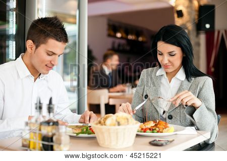 Young cheerful couple on business lunch at restaurant
