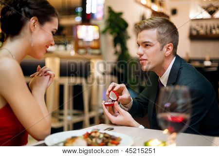 Man proposing to his girlfriend while they are having a romantic date at the restaurant