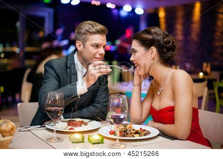 Affectionate couple in restaurant,  him feeding she