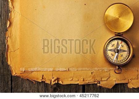 Brújula de bronce antiguo sobre fondo de papel viejo