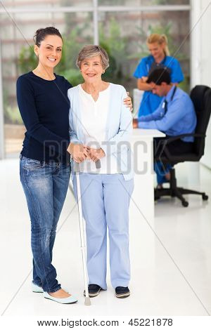 portrait of beautiful daughter taking her elderly mother to doctor