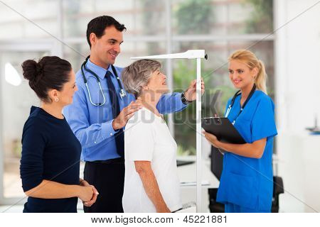 general practitioner measuring senior patient's height in office