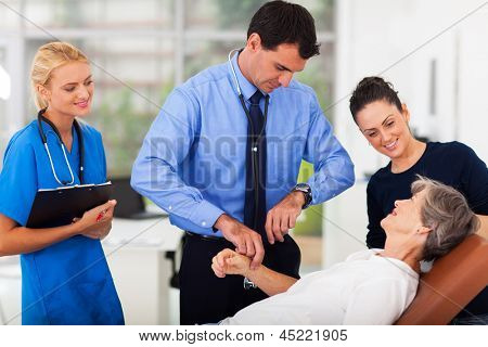 doctor checking senior patient's pulse in office