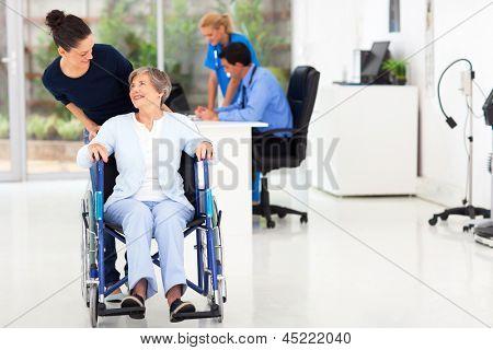beautiful loving daughter taking senior mother visiting doctor